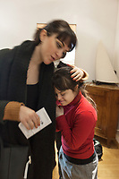 Switzerland. Canton Ticino. Pregassona. Living room.  Margerita Montobbio (23) hugs her young sister Elisabetta (20) before leaving the flat. Elisabetta Montobbio is a dancing member of MOPS_DanceSyndrome which is an independent Swiss artistic, cultural and social organisation operating in the field of contemporary dance and disability. It is composed only of Down dancers. Down syndrome (DS or DNS), also known as trisomy 21, is a genetic disorder caused by the presence of all or part of a third copy of chromosome 21 It is usually associated with physical growth delays, mild to moderate intellectual disability, and characteristic facial features. A sword is a bladed melee weapon intended for slashing or thrusting that is longer than a knife or dagger, consisting of a long blade attached to a hilt. Pregassona is a quarter of the city of Lugano. 1.02.2020 © 2020 Didier Ruef