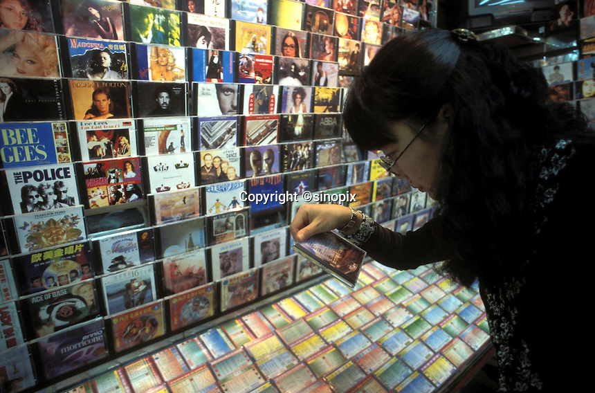 A woman looks at a pirated CD for sale in a shop in Guangzhou, China.