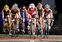 28 JUN 2012 - LONDON, GBR - Liz Blatchford (in pink and black) leads the front pack on the bike during the elite women's heat of the 2012 Canary Wharf Triathlon in Canary Wharf, London, Great Britain .(PHOTO (C) 2012 NIGEL FARROW)