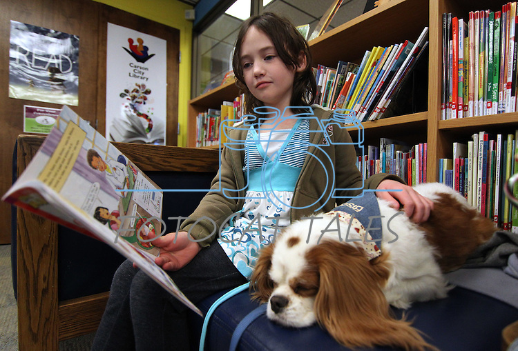 Caitlin Wilhelm, 9, reads to Biscuit during a Love on A Leash event at the Carson City Library, in Carson City, Nev., on Saturday, Dec. 17, 2011. .Photo by Cathleen Allison