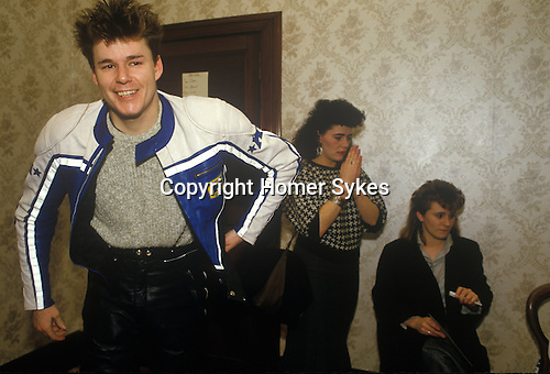 Stuart Adamson, Big Country on tour Scotland. Dressing room with two girl fans, groupies. He is near his family home and will drive his motor bike to go home that evening rather than in the band hotel. 1980s