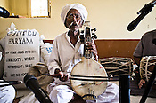 75-year-old Manganiyar artist, Saqar Khan sings and plays his Kamancha (music instrument) during field recordings inside their house in Hamira village of Jaiselmer district in Rajasthan, India. Photo: Sanjit Das/Panos