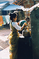 A Goan woman scoops water from a well to pour into her own beaten copper vessel, Goa, India.