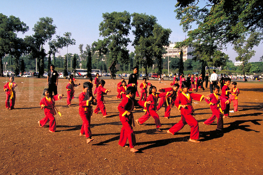 Asian kids participate in Sunday morning martial arts classes in Jakarta, Indonesia city park. sports, children, uniform clothing, child. Martial Arts Class. Jakarta, Indonesia Asia.