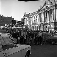 Place du Capitole 11 ou 12 juin 1968. Départ du cortège : vue d'ensemble manifestants (vue de 3/4 face), banderoles ; en arrière-plan façade du Capitole. Cliché pris durant les évènements de Mai 68 à Toulouse.
