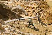 Sand and crystal extraction by two men with high powered hoses and pick axe.