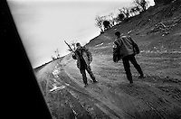 KLA fighters guard a road into Drenica while the Serb police and army attack the village of Polace, a few kilometres away..Kosovo, 22/03/99.