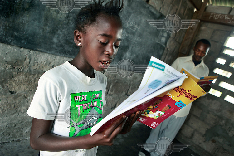 A schoolgirl reads from a new textbook during a lesson.