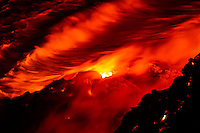 Radiant lava glows inside a vent on a lava bench above the waves, taken from an extremely dangerous cliff near Hawai'i Volcanoes National Park and the Kalapana border, Big Island.