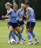 USA forward Natasha Kai dribbles away from teammate Angela Hucles during practice at Shenhua FC in Shanghai, China, on September 25, 2007.