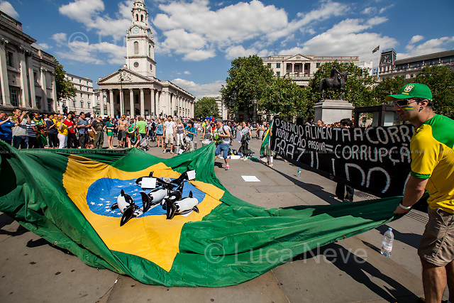 """""""O Silencio Alimenta A Corrupcao. Populacao Passiva = Corrupcao Ativa. Brazil I Do Care"""".<br /> <br /> London, 12/06/2014. Today, on the day of the opening ceremony of the 20th World Cup of Football in Sao Paolo (Brasil), a group of Brasilian people held a demonstration in Trafalgar Square to raise awareness of the problems that are still affecting their country (see photo captions) and in support and solidarity with the protests currently happening in Brasil. Meanwhile, the official """"Brazil Day"""" organised by the Mayor of London was held without disruption in the main square."""