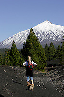 Female hiker with dog hiking through volcanic landscape on south side of Mount Teide Volcano on Tenerife. Canary Islands, Spain