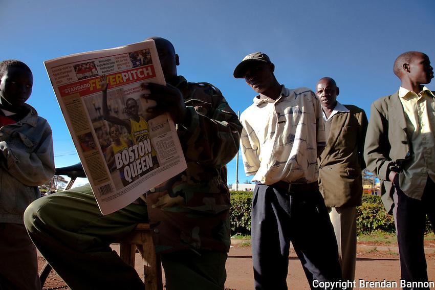 Kenyan men on the streets of Iten, Kenya read about Salina Kosgei's victory in the  2009 Boston marathon..