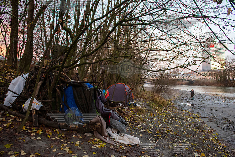 A homeless person's shelter made with branches draped with old tents and sleeping bags beside the Avre River close to the RTS tower, HQ of the French-speaking arm of the Swiss national broadcaster.