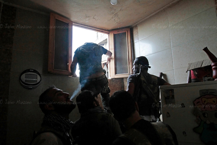 Free Syria Army soldiers exit a building after completing a military operation against loyalist forces holed up in the adjacent apartment building in the Amariya front of Aleppo.