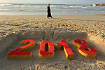A Palestinian woman walks past a 2018 sand writing at a beach in Gaza City on December 31, 2017 on the last day of the year. Photo by Ashraf Amra