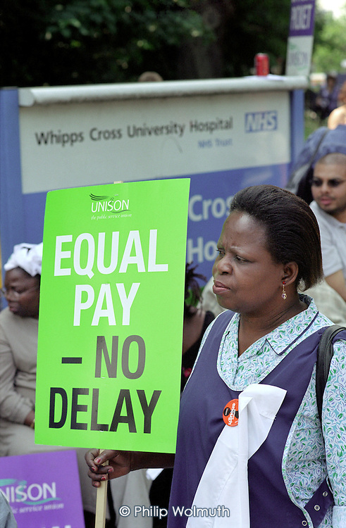 Contract catering, portering and cleaning staff employed by multinational ISS Mediclean picket Whipps Cross Hospital over pay and conditions.  Their campaign for a living wage is backed by Unison and The East London Citizens Organisation (TELCO); Walthamstow, 2003.