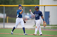 GCL Rays pitcher Justin Montgomery (19) and first baseman Luis Perez (24) celebrate after closing out a Gulf Coast League game against the GCL Pirates on August 7, 2019 at Charlotte Sports Park in Port Charlotte, Florida.  GCL Rays defeated the GCL Pirates 5-3 in the second game of a doubleheader.  (Mike Janes/Four Seam Images)