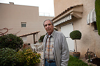 Raoul Repaire, 86, poses for the photographer at his home in Beausoleil, France, 18 October 2013. A retired member the Société des Bains de Mer (SBM), Raoul, years ago, could see as far as the Cap Martin from his house. Now the Tour Odéon, currently under construction, and a modern residence recently built by a Monaco-based real estate agency on the plot of land next to his house (left) block his view southeast.