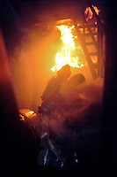 Firefighters attack a simulated kitchen fire inside the fire training burn trailer during training with the Occidental Volunteer Fire Department
