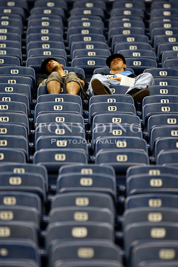 Victor Camcho, left, and Edwin Cisneros, both from Reston, Va., take a nap in their Ford Field seats before a preseason NFL football game between the Detroit Lions and Buffalo Bills, Thursday, Sept. 2, 2010, in Detroit. (AP Photo/Tony Ding)