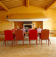 The large table in the dining room is dwarfed by the ancient inglenook fireplace