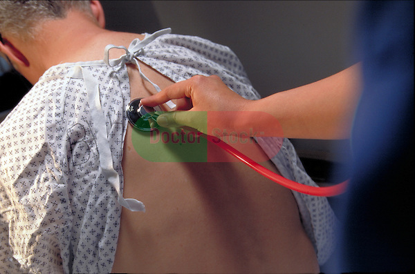 nurse's hand holding stethoscope on upper back of male patient
