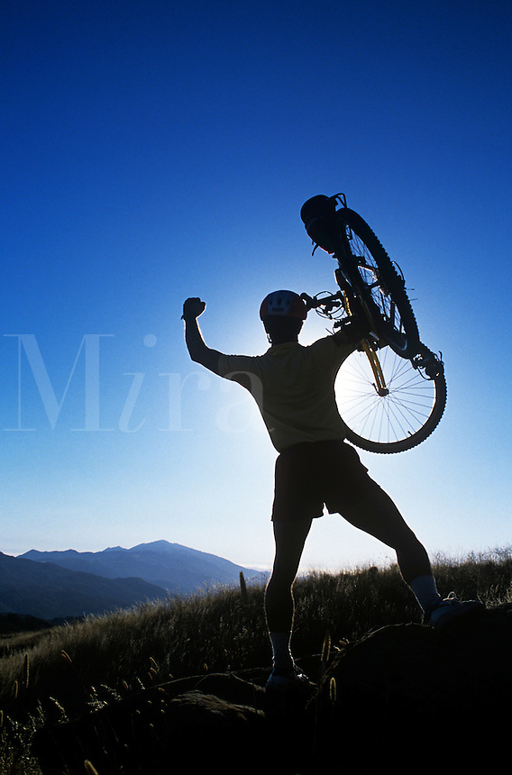 Mountain biker celebrating after reaching the sumit