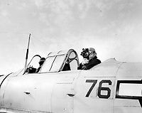 The Photo squadron personal, planes, and cameras equipment.  An Eyemo being used in an SNJ braced on a tripod.