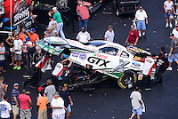 Sept. 15, 2012; Concord, NC, USA: NHRA crew members for funny car driver Mike Neff in pits surrounded by fans during qualifying for the O'Reilly Auto Parts Nationals at zMax Dragway. Mandatory Credit: Mark J. Rebilas-