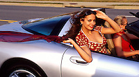 A smiling young woman looks out as she rides in a silver Corvette convertible.