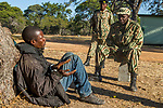 Arrested poacher being questioned by anti-poaching commanders, Kafue National Park, Zambia