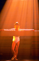 Young girl gymnast bathed in golden sunlight has arms outsrtrecthed along a balance beam.