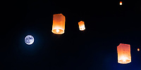 Floating lanterns soaring in the dark sky with beautiful full moon, during Loy Krathong Yee Peng festival, in Chiang Mai Thailand
