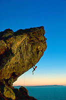 A rock climber hangs perilously by two hands from Endless Bumper in Marin County, California with the glow of sunset and the Pacific Ocean behind him.<br />