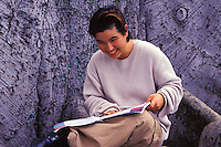 Young local girl with school papers and backpack studies near a big tree at a park