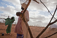 """Kenya/Somali refugees. Dugow and his wife, Wilo, left Dinsor, Somalia """"because of the war, and the hunger.  We are farmers and have not planted crops in 2 years. Our cows could not graze because of the drought. Six died and we sold the last five for $8.00 each. 2 years ago we would have gotten $150.00 each for them. We used the money from the sale to flee to Kenya.  Al Shabaab is arresting people who seek aid so there are no agencies in our area. We are from the bush and could avoid the the worst of the war but now to survive you need the town and the town means war,"""" said Dugow, in Dagahaley camp near Dadaab, Kenya."""