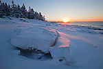 Sun rises at snow covered Schoodic Point in winter on the Schoodic Peninsula in Acadia National Park, Maine, USA