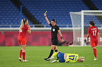 YOKOHAMA, JAPAN - AUGUST 6: Referee Anastasia Pustovoytova gives a yellow card to Janine Beckie #16 of Canada during a game between Canada and Sweden at International Stadium Yokohama on August 6, 2021 in Yokohama, Japan.