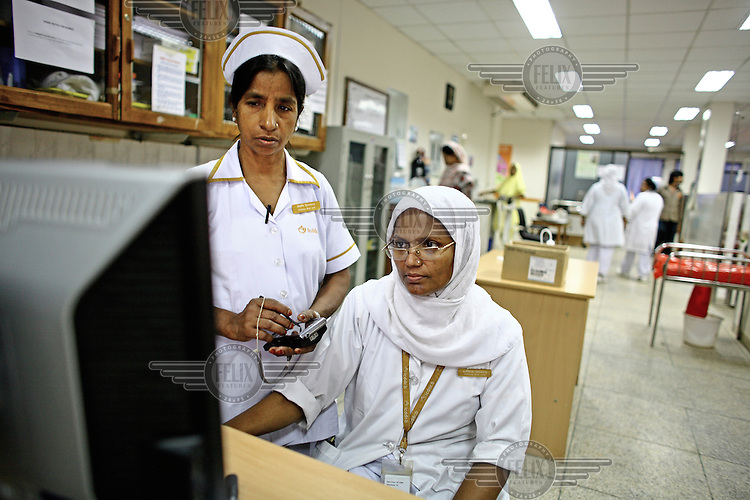 Nurses check a computer and one records information onto a hand held device, at the International Centre for Diarrhoea Disease Research, Bangladesh (ICDDR B). The ICDDR is an international health research organization established in 1978 and credited with discovering oral dehydration therapy for the treatment of diarrhoea and cholera.