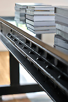 A detail of an iron table with a polished top. Stacks of books are arranged on the table top.