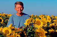 Portrait of a smiling man standing in a field of sunflowers.