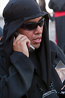 Antigua, Guatemala.  A cucurucho in black, using cell phone, accompanies a Good Friday float in a religious procession during Holy Week, La Semana Santa.