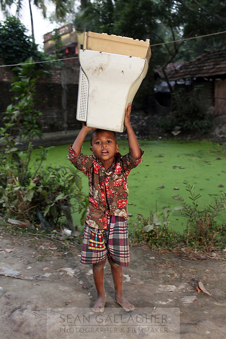 In the village of Sangrampur, a young boy carries an old computer monitor, which he will deliver to villagers nearby who recycle e-waste as a source of income. Kolkata, India. November, 2013