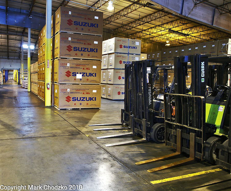 Large interior warehouse facility with boxes of Suzuki motorcycles and forklifts.