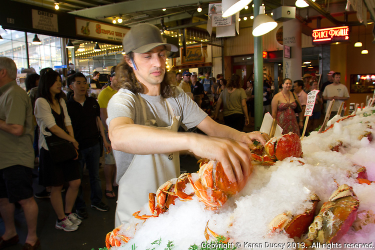 Jaison Scott, assistant manager at the Pike Place Fish Market, arranges dungeness crab in ice in Seattle, Wash., on July 1, 2013. (photo © karenducey.com)