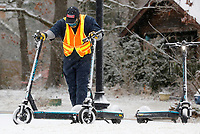 Christian Thompson, with VeoRide, moves a group of electric scooters Friday, February 12, 2021, from Gulley Park into a a sheltered area to protect them from the forecasted winter storms predicted to impact the area. According to the National Weather Service, two winter storms could hit Northwest Arkansas over the next week bringing a chance for up to 12 inches of snow. Check out nwaonline.com/210213Daily/ and nwadg.com/photos for a photo gallery.<br /> (NWA Democrat-Gazette/David Gottschalk)