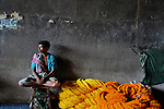A Flower seller waits for customer at Mullick Ghat flower market in Kolkata, Nearly 2000 flower growers sell their produce in this market. These flowers are also exported to West Asia and Europe, West Bengal is the third largest flower producer in India after Karnataka and Tamil Nadu. West Bengal alone produces 6500 tonnes of flower each year. Kolkata, West Bengal, India, 2009, Arindam Mukherjee