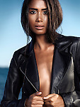 Sexy young woman wearing a black leather jacket over shiny sun tanned body at the beach Image © MaximImages, License at https://www.maximimages.com