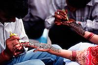 Indian female?Äôs palms decorated with henna design (mehndi), India